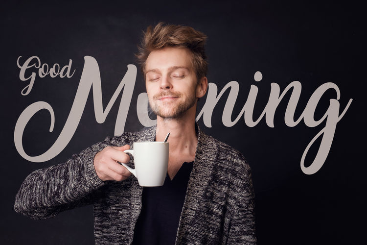 Young Man Having Coffee Against Blackboard With Good Morning Text