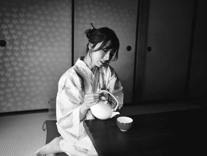Woman holding cup while sitting on table at home