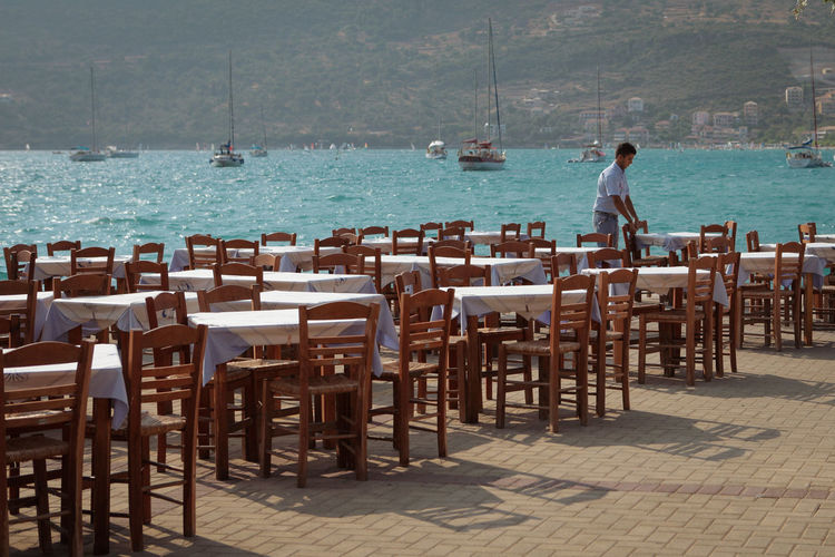 Greek seafront restaurant seating with sailboats in the background Chair Sea Table Water Seat Nature Day Travel Destinations Trip Vacations Outdoors People Cafe Architecture Holiday Travel Leisure Activity Restaurant Wood - Material Seating