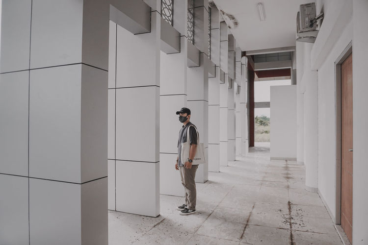 Full length of young man standing against building