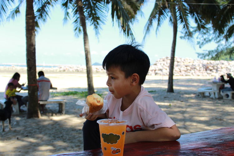 Arunothai Beach Beach Boys Child Childhood Day Drinking Focus On Foreground Food Food And Drink Innocence Land Leisure Activity Males  Men Nature Outdoors Portrait Real People Sitting Tree