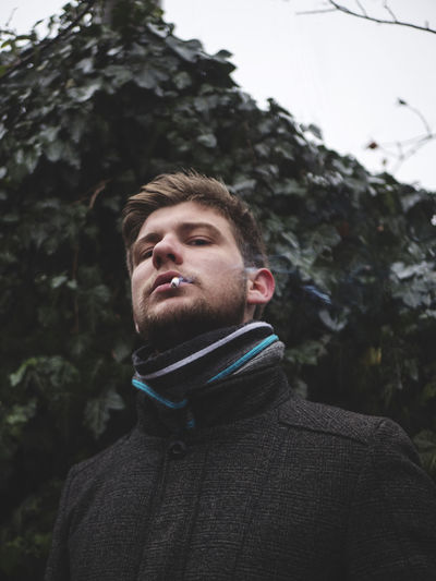 Portrait Of Young Man Smoking While Standing Against Trees In Winter