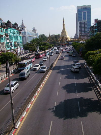 Sule Pagoda Road to Sule Pagoda Blue Sky Buddhist Architecture Buddhist Pagoda Buddhist Temple Cars City City Life Cityscape Composition Distant View Full Frame Gold Stupa High Angle View Myanmar No People On The Move Outdoor Photography Sule Pagoda Sule Pagoda Road Sunlight And Shadows Traffic Transportation Travel Destination Trees Yangon