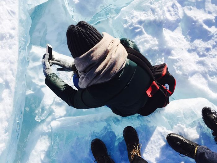 High angle view of person photographing while standing on snow covered field