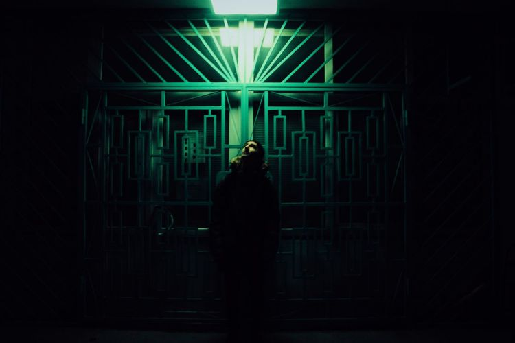 Thoughtful Man Standing By Closed Gate At Night