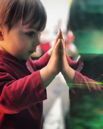 Close-Up Of Boy Standing By Glass Wall