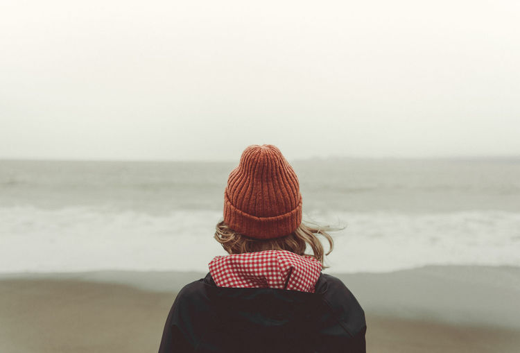 Rear view of woman wearing knit hat against sea at beach