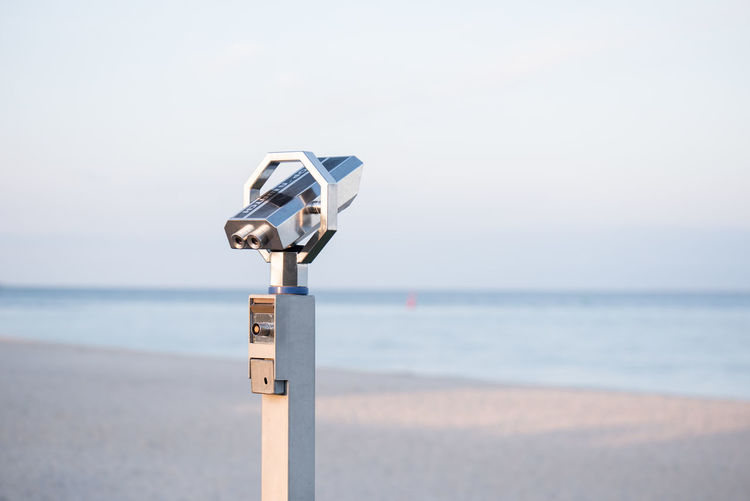 Close-up of coin-operated binoculars on beach against sky