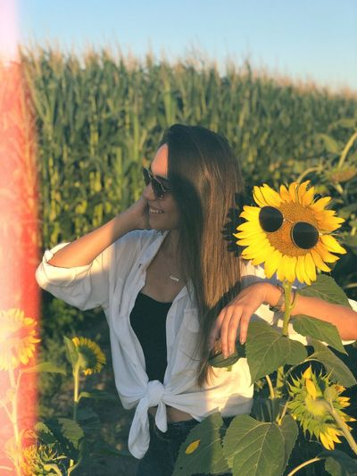 Woman wearing sunglasses while standing by sunflower plants against sky