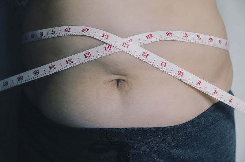 Close-up of human body and fat body, Fat body part of paunch or belly, Overweight of people or excess weight with measuring tape. Body & Fitness Diet Heavy Measuring Obesity Overweighted Stomach Abdomen Belly Body Care Body Part Dieting Fat Father Human Human Abdomen Human Body Part Measurement Obese Overweight People Tape Tape Measure Weight Weights