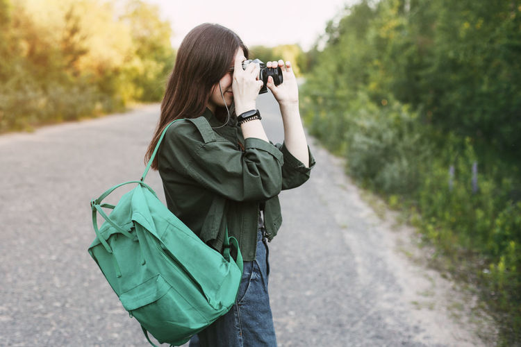 Cute brunette looks at the camera lens. a girl photographs nature.