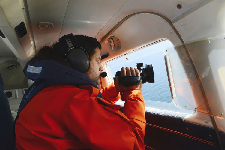 Side View Of Man Shooting Video In Airplane