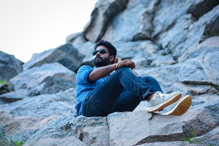 Young bearded man sitting on rock and posing