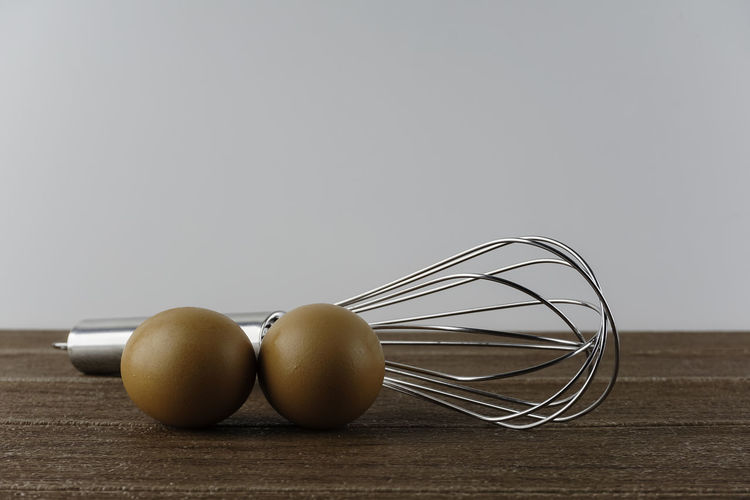 Close-up of eggs in container on table against white background