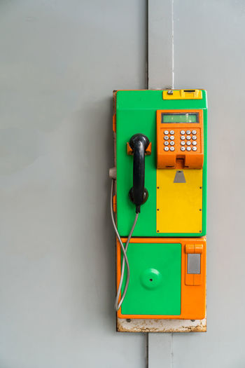 Green and orange vintage public pay phone isolated on white background Green Retro Service Call Coin Communication Money Pay Payphone Phone Public Style Talk Vintage