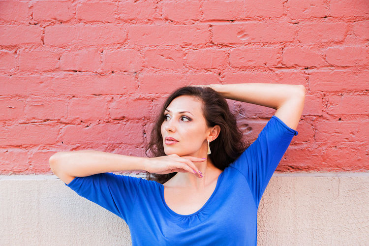 Close-up of thoughtful woman standing against brick wall