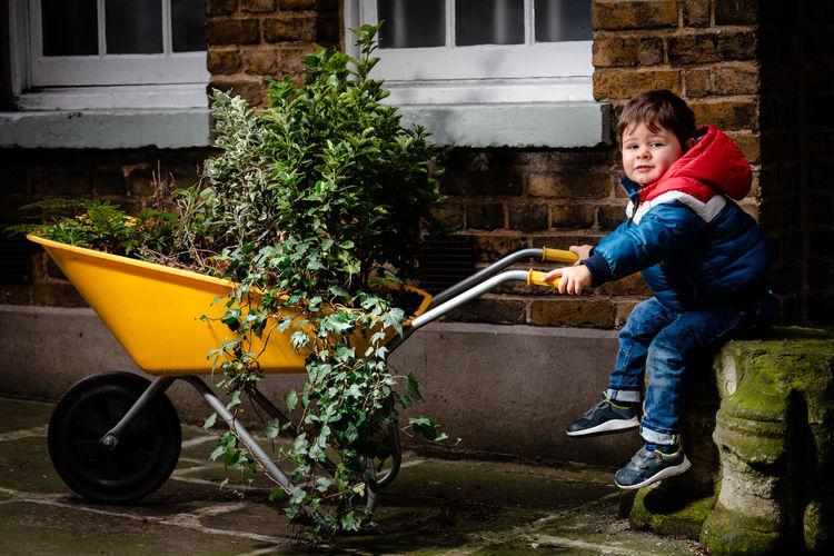 Full length of boy holding plant in yard