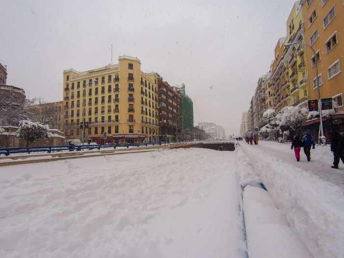Road by buildings in city against sky during winter