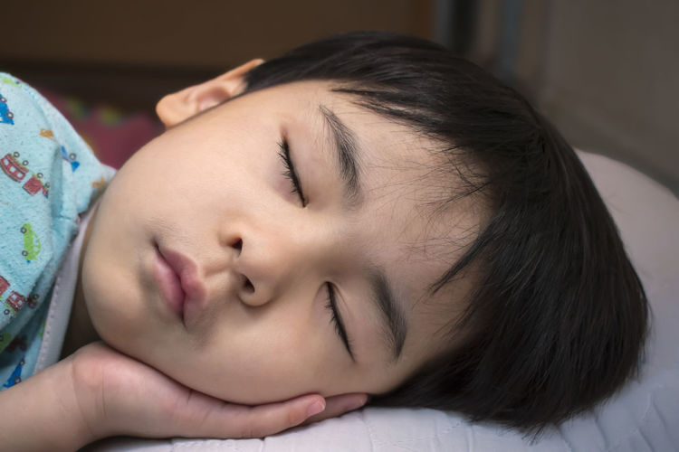 Close-Up Of Young Boy Sleeping On Bed