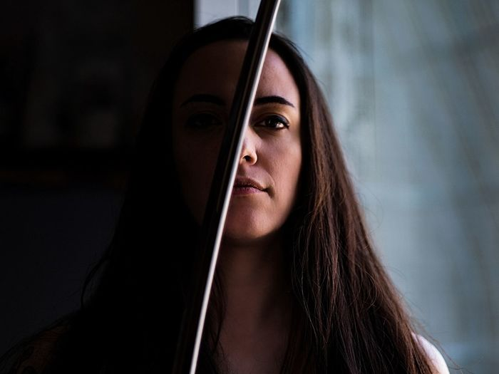 Portrait of young woman by metal rod at home