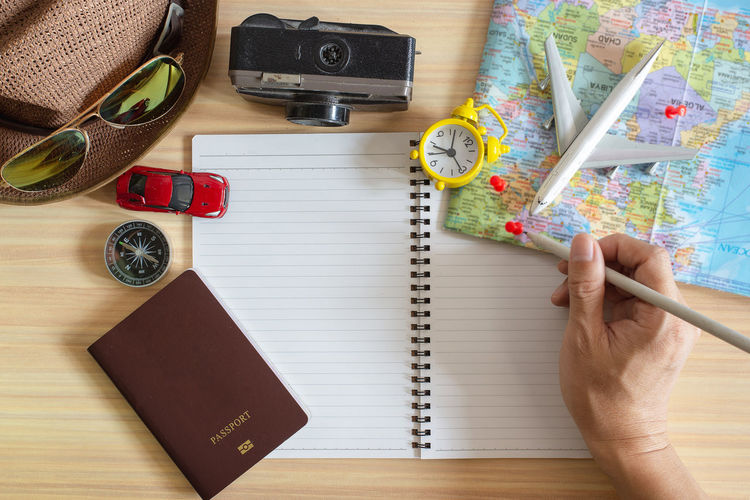 Table Map Indoors  Pen High Angle View Human Hand Directly Above Hand Travel Holding People Camera - Photographic Equipment Adventure Publication Human Body Part Book Photography Themes Trip Vacations Finger Note Pad Travel Accessories Planning Map Notebook Passport Clock Camera Compass Hat Car Airplane