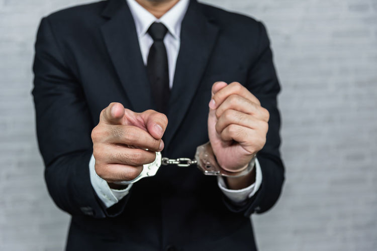 Midsection of businessman with hands trapped with handcuffs