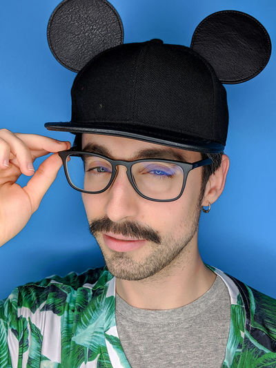 Humor Goodfeelography Portrait EyeEm Team Looking At Camera Smiling One Person Eyeglasses  Hat Mickey Fun Headshot Front View Glasses Lifestyle Human Face Young Men Casual Clothing Beard Making A Face Leisure Activity Blue Background Blue My Best Photo