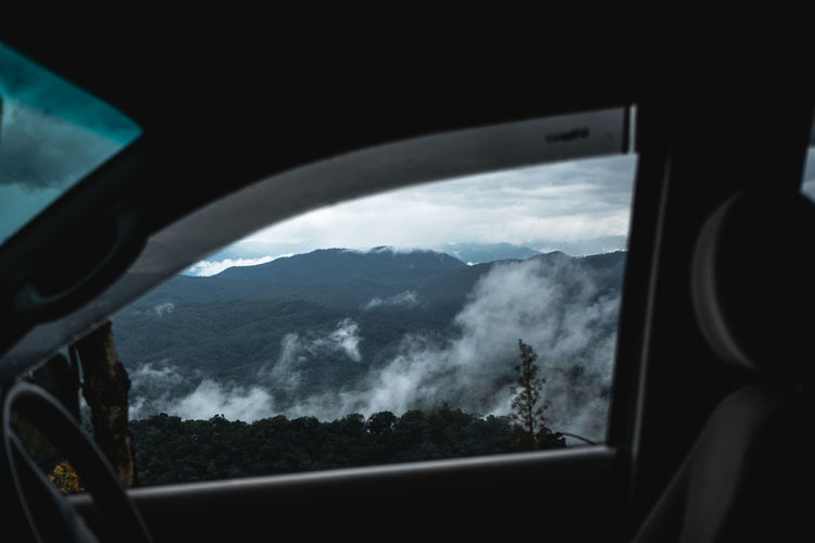 Scenic view of clouds seen through car window