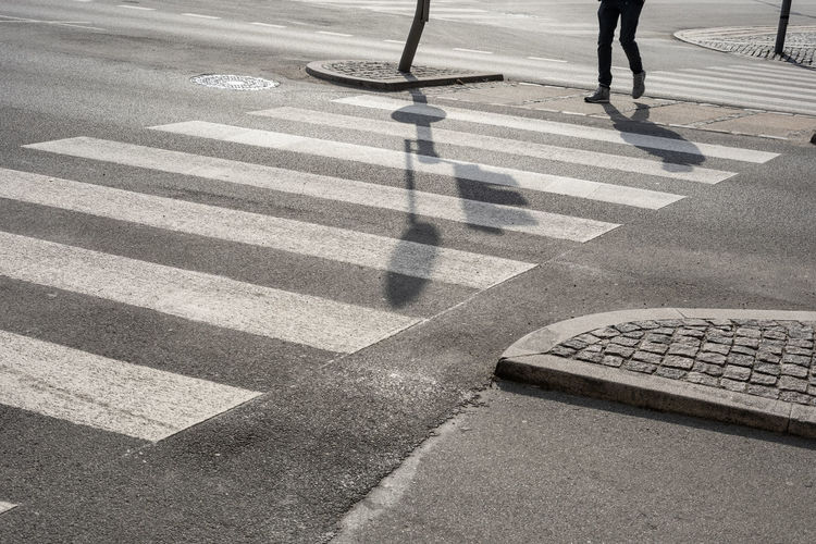 Low section of person crossing road