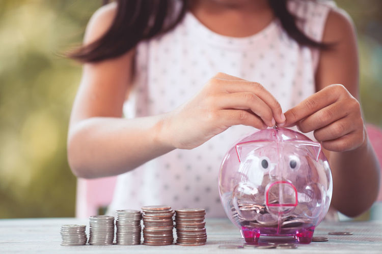 Midsection of girl putting coins in piggy bank on table