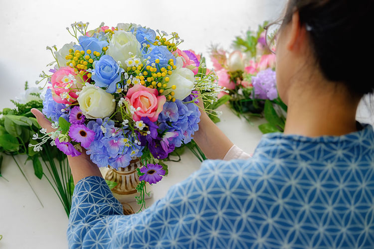 Midsection of people with flower bouquet