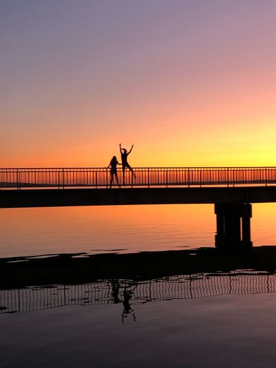 Silhouette people standing on bridge against sky during sunset