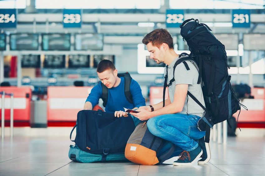 Two friends traveling by airplane. Travelers preparing their passports and airplane ticket at the airport check-in. Airport Airport Departure Area Airport Runway Backpacker Backpacking Baggage Check In Connection Departure Handsome Journey Leaving Lifestyles Luggage Passenger Passport Real People Togetherness Tourism Tourist Travel Traveler Traveling Trip Two People