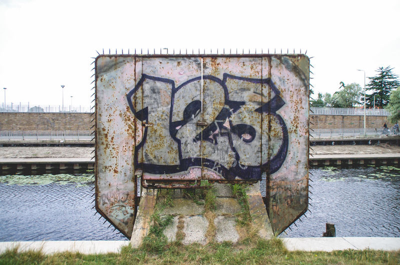 Graffiti Built Structure Canal Day Metallic No People Rusty Water Weathered