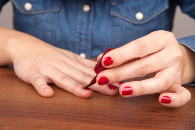 Midsection of woman painting fingernails at table