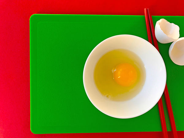 Egg with chopsticks on cutting boards Asian  Bowl Chopsticks Closeup Colorful Contrast Copy Space Cutting Boards Day Egg White Egg Yolk Eggshells Food Preparation Geometric Shapes Green Indoors  Natural Light No People Overhead Phone Camera Raw Egg Red Textures White