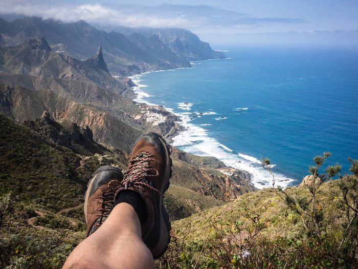 Hiker in Anaga Mountains, Tenerife, Canary Islands, Spain Resting Sitting Man Mountain SPAIN Tenerife Hiker Hiking Personal Perspective Sea Water Human Body Part One Person Shoe Low Section Real People Beauty In Nature Outdoors Day Human Leg Nature