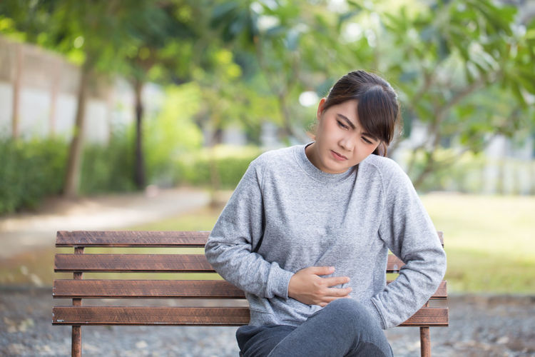 Young woman with stomachache sitting on park bench