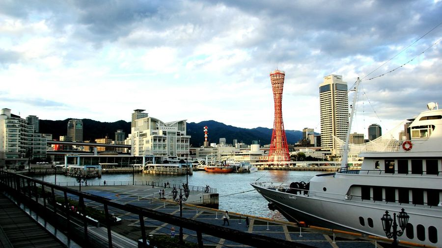 Kobe Port Tower Amidst Buildings In Front Of River Against Cloudy Sky At Harbor