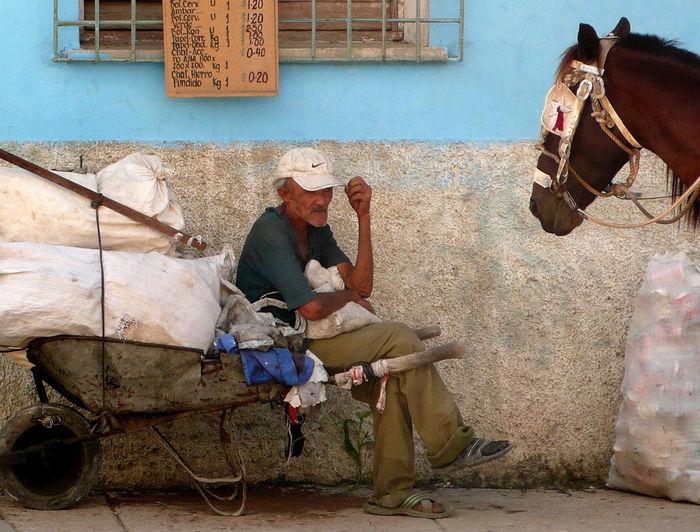 Man sitting on wheelbarrow with horse by wall