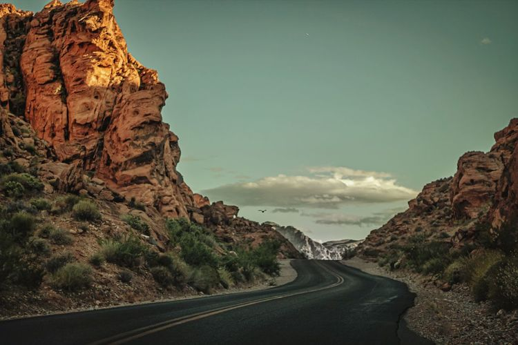 Road amidst rock formation against sky