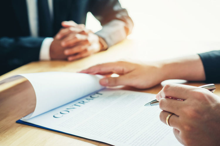 Midsection Of Businessman Signing Contract On Table