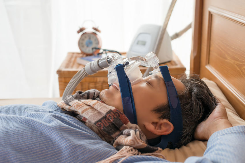 Man and cpap mask.Middle aged man with obstructive sleep apnea symptoms sleeping well on his back by wearing cpap mask,healthcare concept. Back Choking Continuous Positive Airway Pressure Home Snoring Tube Concept Cpap Healthy Lifestyle Mask Obstructive Sleep Apnea Senior Men Sleep Apnea Sleeping Symptoms