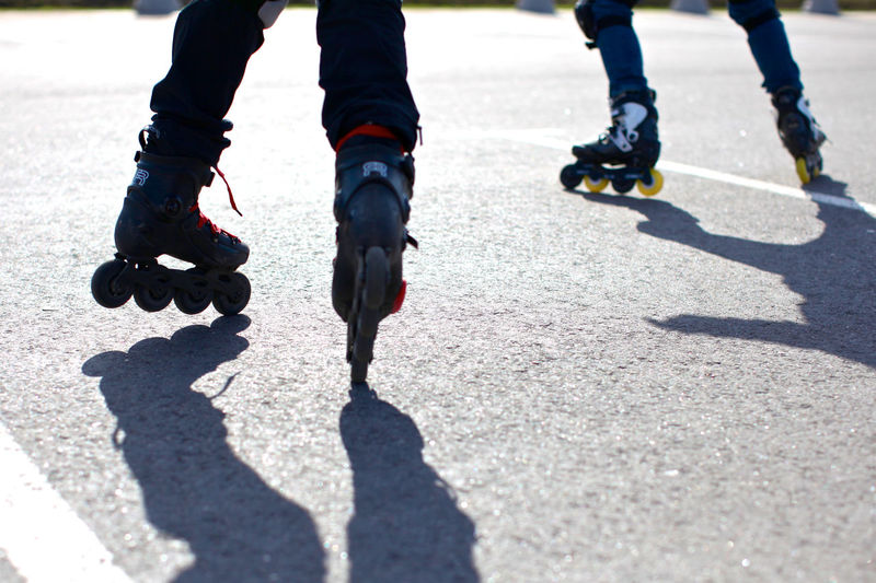 Low Section Of People Roller Skating On Road