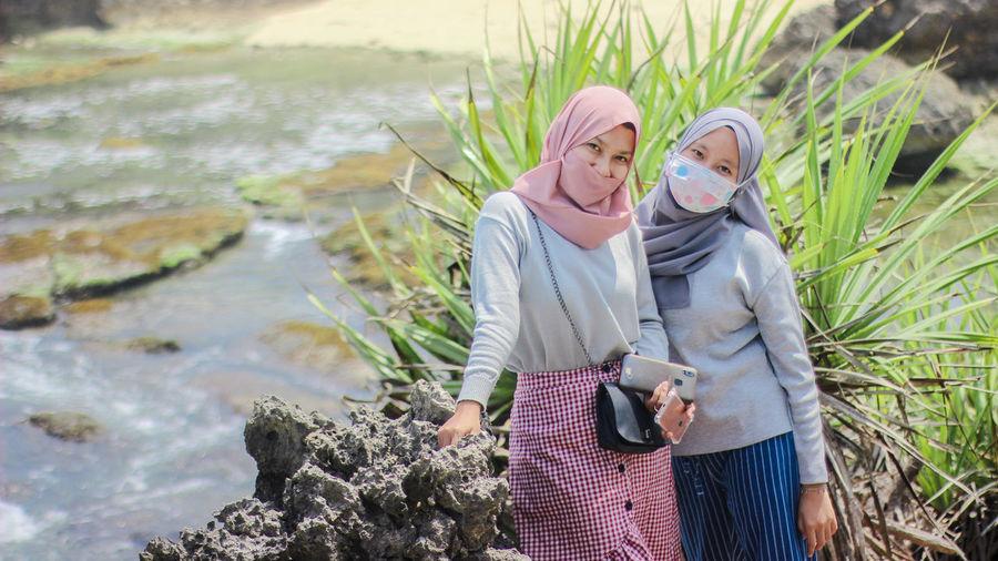 Portrait of women wearing pollution masks standing by rock