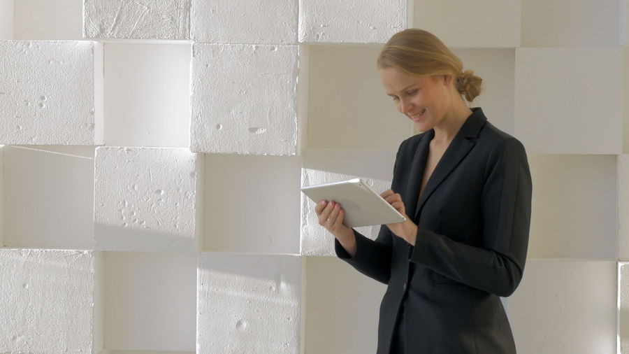 Woman holding mobile phone while standing against wall