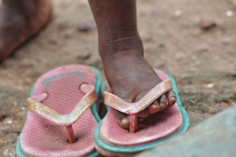 Low section of girl wearing flip-flop on land