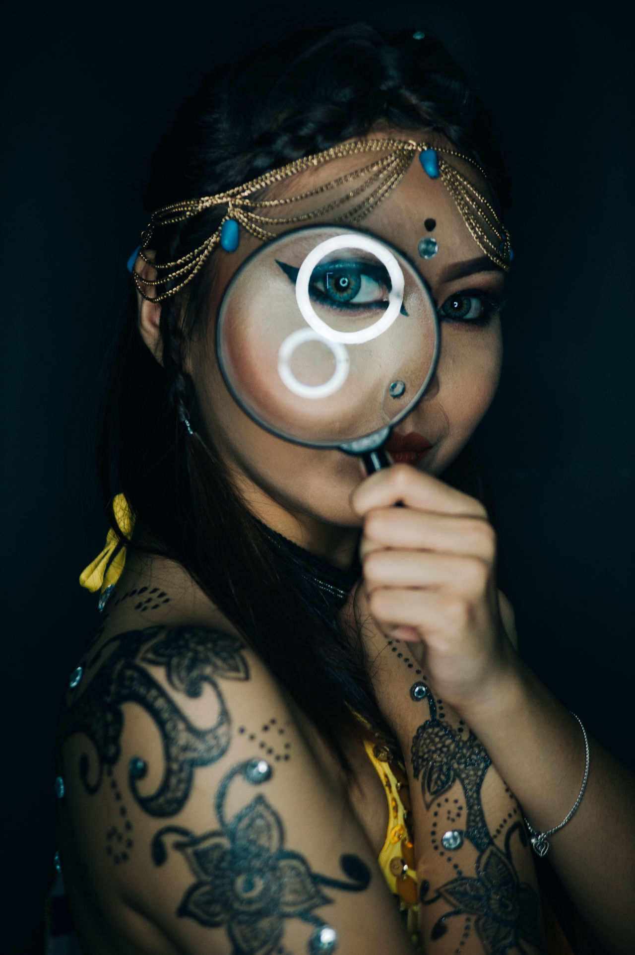 Close-up of tattooed woman looking through magnifying glass against black background