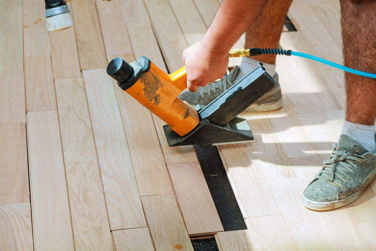 Low Section Of Man Working On Hardwood Floor