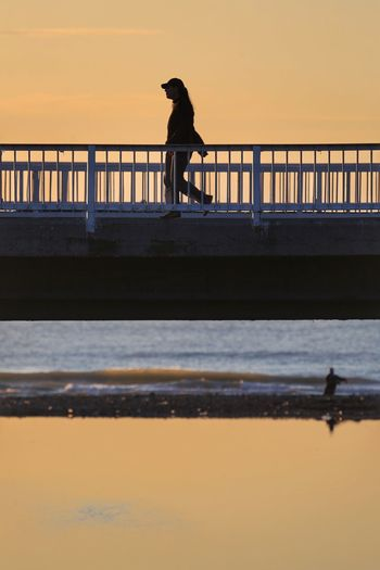 Low Angle View Of Woman Walking On Bridge Against Sky During Sunset